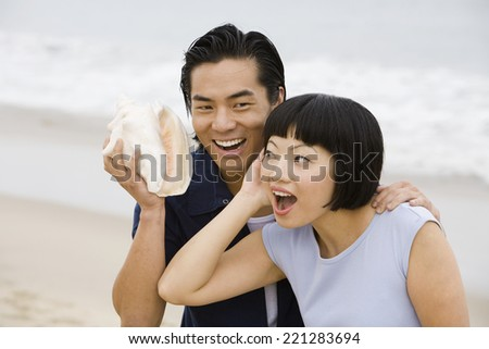 Asian couple holding conch shell - stock photo