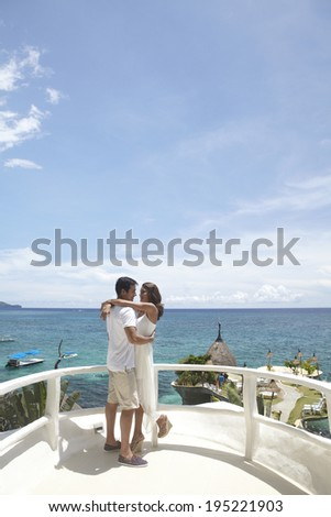 Asian couple holding hands by the sea in Boracay in Philippines