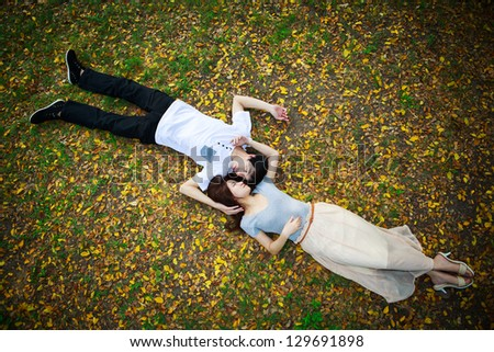 Asian couple laying down outdoor in park looking happy on fall ground - stock photo