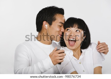 Asian couple listening to mp3 player