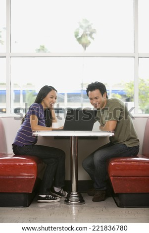Asian couple looking at laptop - stock photo