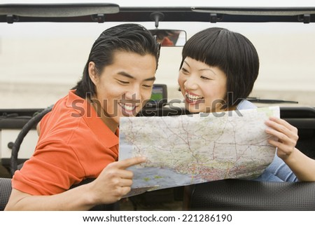 Asian couple looking at map - stock photo