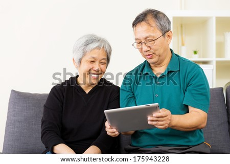 Asian couple looking at tablet together - stock photo