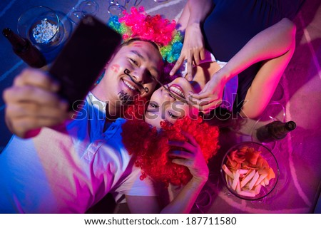 Asian couple making a selfie during a party - stock photo