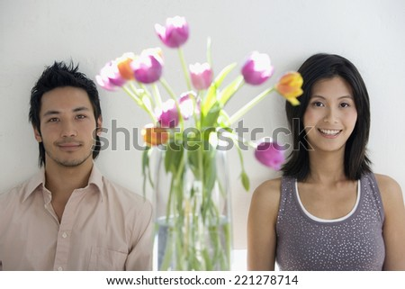 Asian couple next to flowers in vase - stock photo