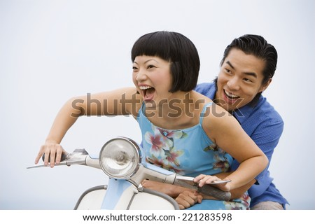 Asian couple riding motor scooter - stock photo
