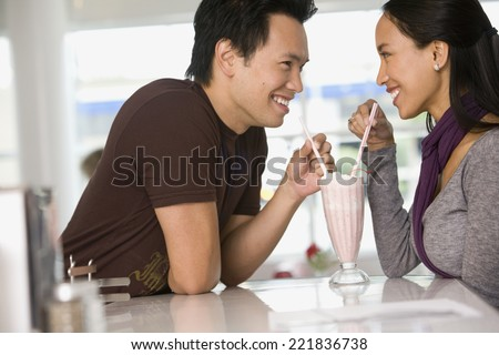 Asian couple sharing milkshake - stock photo