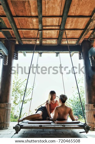asian couple sitting in hanging bed, in the middle of the garden overlooking the northern hills