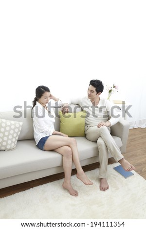 Asian couple sitting on couch