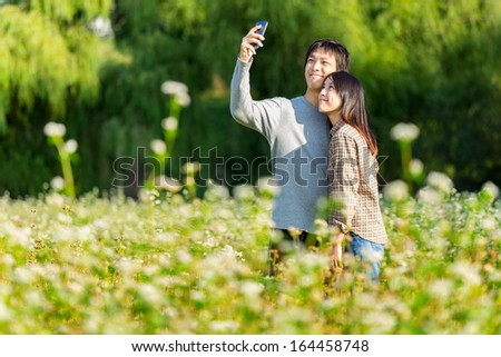 Asian couple take photo by mobile phone - stock photo