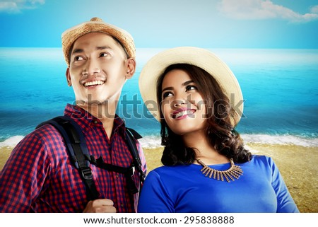 Asian couple travel along on the beach at the summer - stock photo