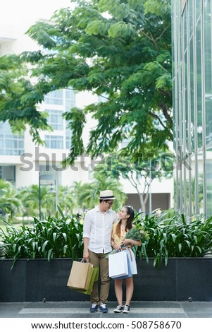 Asian couple with flowers and shopping bags standing outdoors