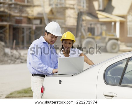 Asian couple with laptop at construction site - stock photo