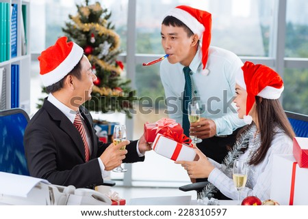 Asian coworkers having celebration of  Christmas in the office