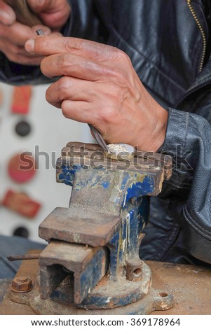 Asian craftsman making personalized stamp  on the street in Hanoi