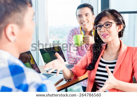 Asian creative agency workers discussing and explaining new project - stock photo