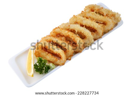 Asian Cuisine, Chinese dishes, Oven-Fried Onion Rings,dipped in batter,  lie in a row on a long white plate, with a green sprig of parsley and lemon isolated on a white background. - stock photo