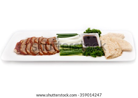 Asian Cuisine Dish Peking Duck Laying On A White Plate With Vegetables Sauce And Cake