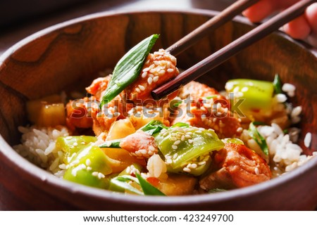 Asian cuisine - rice in sauce with stir fried vegetables, pineapple and salmon. Wooden bowl with chopsticks. Close up.