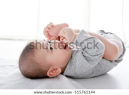 Asian Cute baby lying on the bed takes feet in mouth, photography in the studio