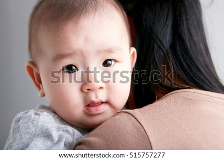 Asian cute baby,nestled on her mother's shoulder