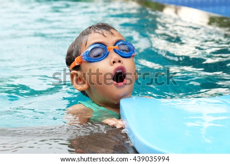 asian cute boy enjoy swimming in pool - stock photo