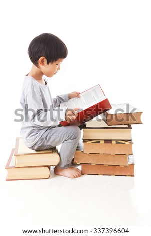 Asian cute boy reading book while sitting on stack of books. white background. - stock photo