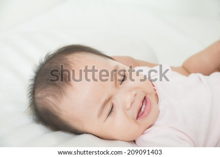 Asian cute girl baby crying in bed
