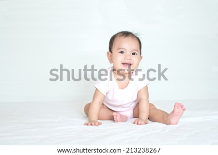 Asian cute girl baby is smiling in bedroom