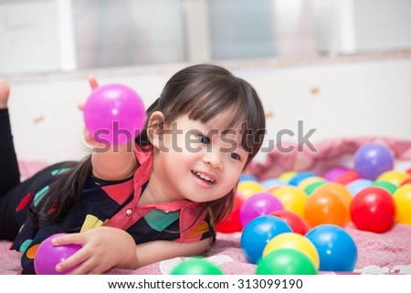 Asian cute girl playing ball toy. - stock photo