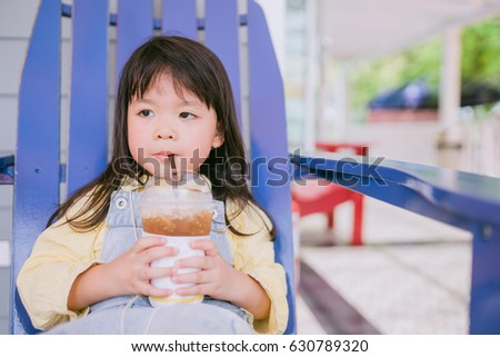 Asian Cute little girl drinking Lemon soda from glass on the house.