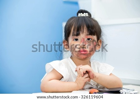 Asian cute little girl. Makeup Cosmetics Fun and pleasure (concept of Halloween).