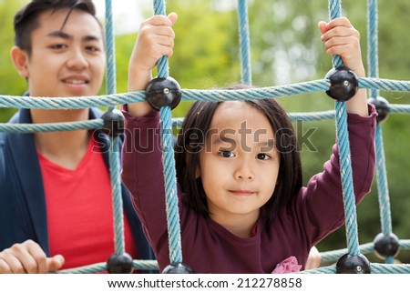 Asian dad and daughter on a playground - stock photo