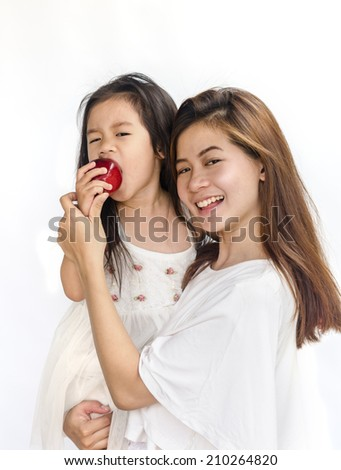 Asian daughter and mom eating red apple isolated on white. - stock photo