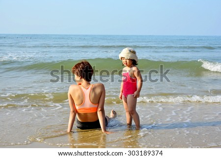 Asian daughter crying try to talk with mother on the beach