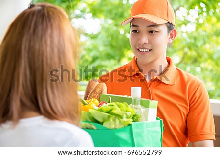 Asian delivery man delivering food to a woman at home - online grocery shopping service concept