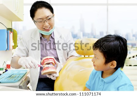 Asian dentist showing a boy  how to brush his teeth properly - stock photo