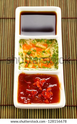 Asian dipping sauces consisting of chilli sauce, soy sauce and cucumber and parsley sauce. - stock photo