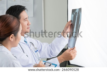 Asian doctor and his colleagues looking at the chest x-ray - stock photo