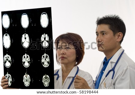 Asian Doctor and Nurse looking at patients MRI or x-ray - stock photo