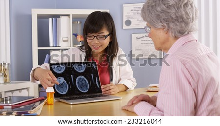Asian doctor explaining brain scans to elderly patient - stock photo