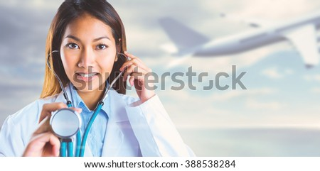 Asian doctor holding her stethoscope against bridge over water and blue sky