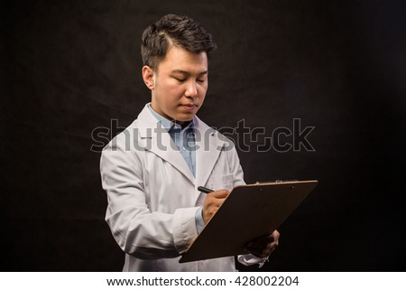 Asian doctor. Mature Chinese male medical doctor standing isolated on white background. Handsome Asian model portrait. - stock photo
