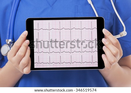 Asian doctor or nurse holding a tablet computer showing an EKG.  With a Clipping Path on the screen - stock photo