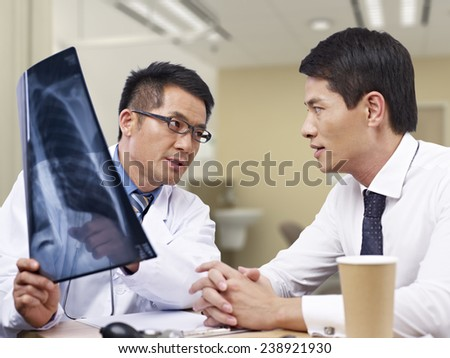 asian doctor talking to patient about x-ray result. - stock photo