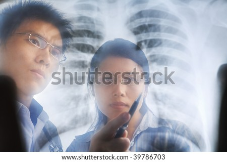 Asian doctors having discussion over x-ray print/ roentgen.