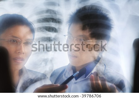 Asian doctors having discussion over x-ray print/ roentgen
