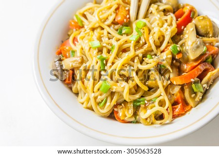 Asian egg noodles with vegetables, mushrooms, green onions and sesame - stock photo