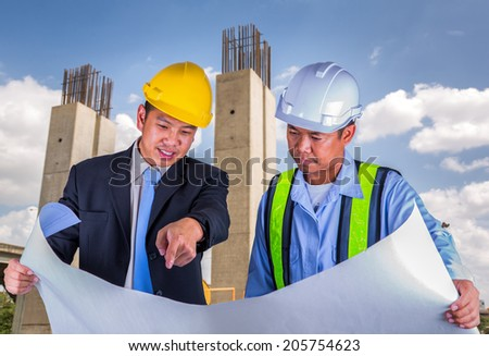 Asian engineer and worker leader discus for drawing detail in construction site