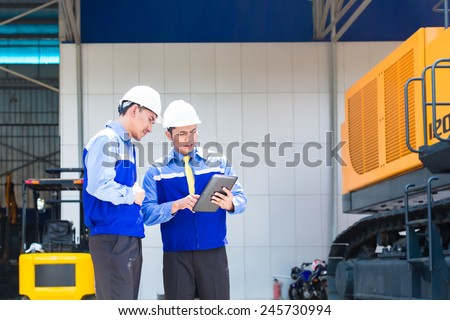 Asian engineer controlling construction machinery of construction site or mining company - stock photo